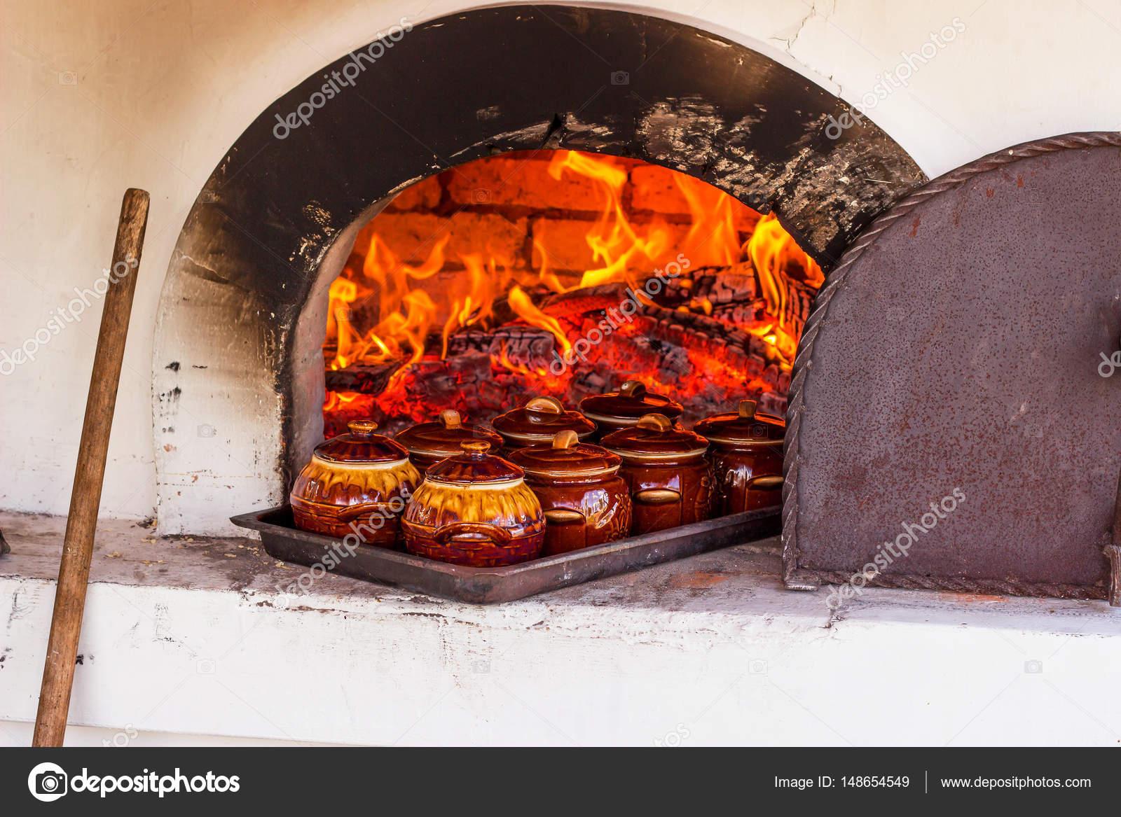 Cocinar en el horno en una olla de le a con alimentos - Cocinar en horno de lena ...