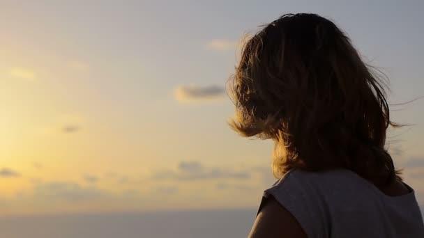 einsame junge Frau, Blick auf das Meer bei Sonnenuntergang wie der Wind die Haare bewegt
