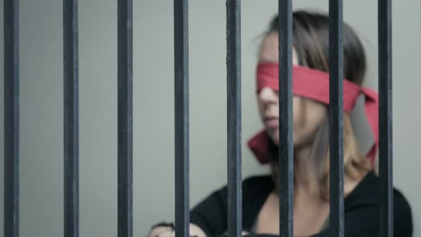 young woman blindfolded behind prison bars