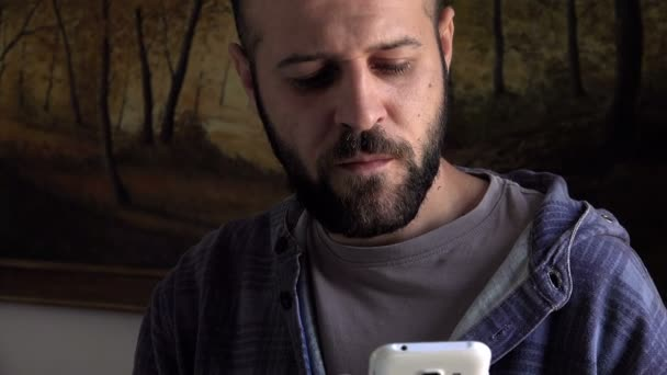 young man chat with cell phone while drinking a coffee