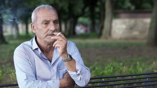 Rentner auf Bank zündet sich Zigarette an