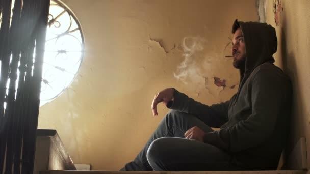 portrait of drug dealing: drug dealer sitting on the stairs sells drugs