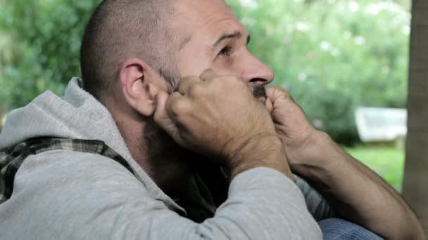 elmebeteg férfi egy parkban dörzsöli az arcát a kezével