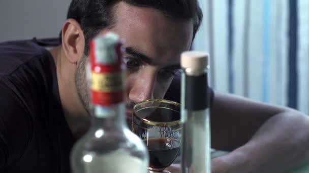 Opilý mladík opřel se o stůl a zoufalé doušek vína