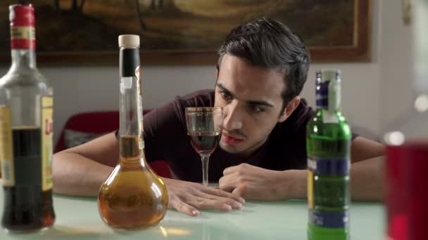 opilý muž hledí na svou sklenku s alkoholem