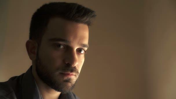 mladý muž s bradkou vypadá dopředu