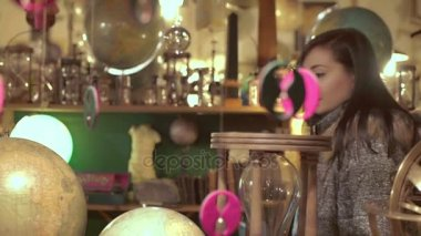 happy woman uses a globe in an antique shop