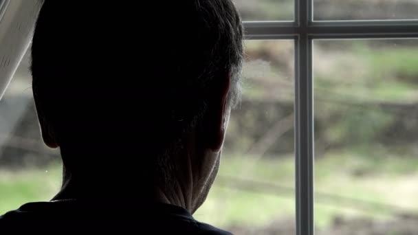 muž ve stínu, opřel se okna a díval