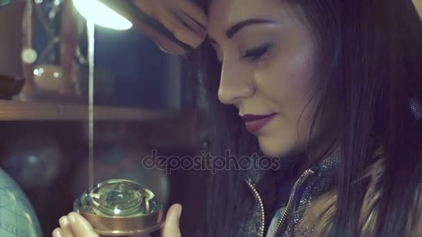 young woman plays with ancient compass