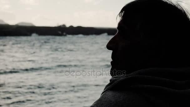zamyšlený člověk ve stínu, v blízkosti moře