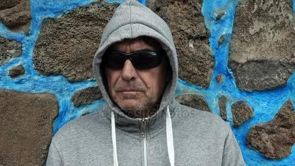 zloděj je skryta s kapucí a sluneční brýle