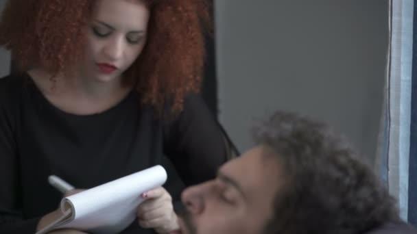 rusovlasá mladá psycholožka trvá poznámky poslouchá svého pacienta