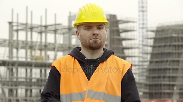 dělník na stavbě vypadá vážným fotoaparátu