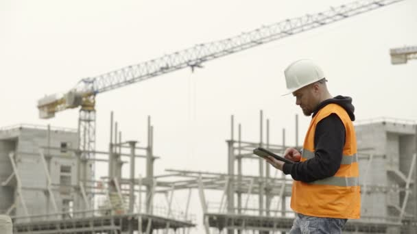 young engineer in the construction yard controls the project on tablet