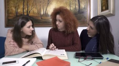 three young girls chatting and laughing while going over the lesson