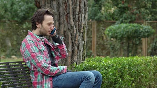 muž sedí na lavičce mluví po telefonu s přítelem šťastně