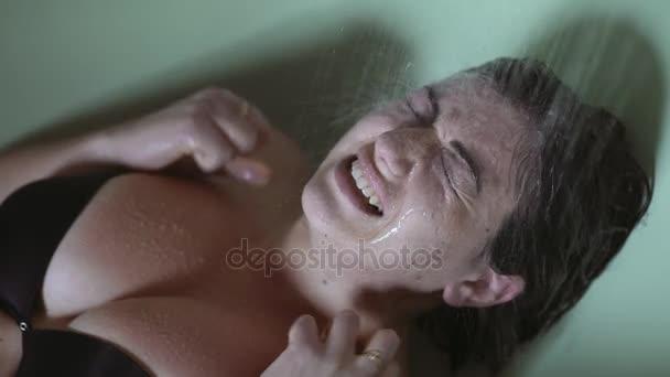 zoufalá žena ležet ve vaně, utrpení, zatímco voda přichází do tváře