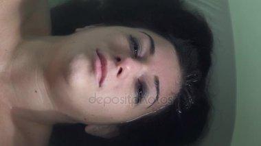 depresivní, smutné mokré žena leží ve vaně