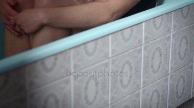 depressziós nő ül a kádban, míg a víz nedvesíti a haj