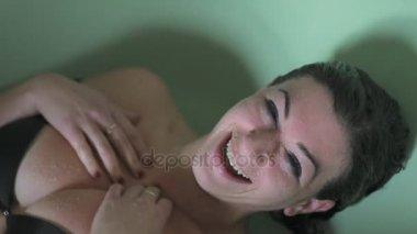boldog és mosolyog, kádban víz alatt fekvő nő