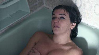 szomorú és átgondolt nő feküdt a fürdőkádban, míg a víz twets az arcát