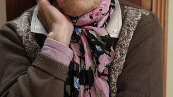 alte Großmutter sitzt und schaut in die Kamera und schließt die Augen