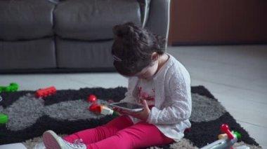 kis lány ül a földön szándék, és a játék a smartphone