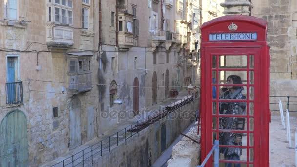 woman in red telephone box in a small village- Valletta, Malta