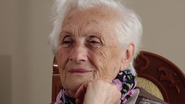 Velmi stará žena se usmívá na kameru