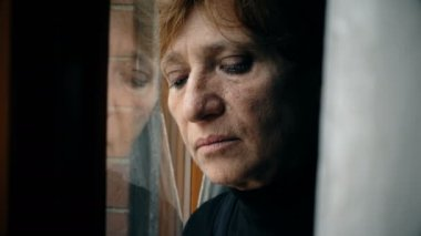 Close up on sad and depressed mature woman leaning against the window