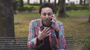 Angry nervous  man talking on the phone sitting on a bench