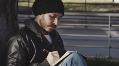 Young student sitting under a tree writing in a notebook