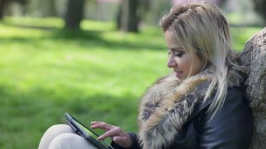 Cute smiling blond woman sitting under a tree using tablet computer