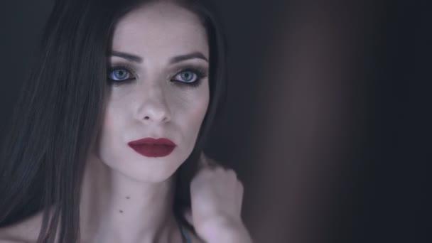 Krásná a sexy žena dotýká její vlasy před zrcadlem s úsměvem