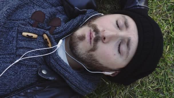 Okouzlující a pohodový chlap ležící na trávníku, poslouchat hudbu pomocí sluchátek