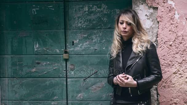 traurige, aufgebrachte, einsame blonde Frau in der Nähe des grünen Tores