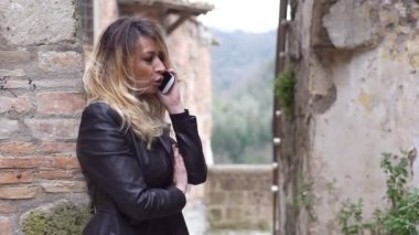 Beautiful  blonde woman happily talking on the mobile phone- outdoor