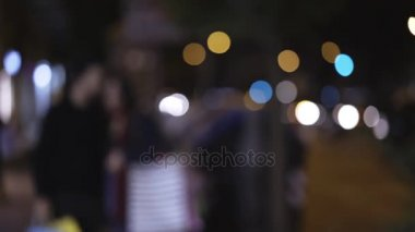 Blurred couple walking and chatting on the street at night