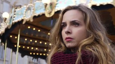 Depressed sad blond woman with carousel running in the background