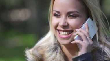 Beautiful and smiling woman talking on the phone at the park, close up