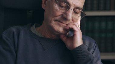 Sad  alone old man looks at the camera and closes his eyes