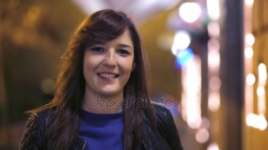 Beautiful brunette walking on the street and smiling at the camera, at night