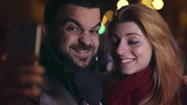 Smiling couple doing funny selfie at night in the city,close up