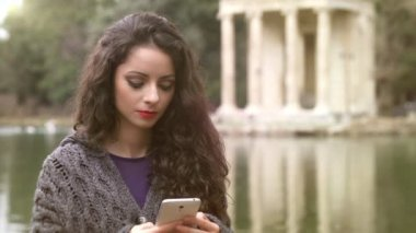 Beautiful brunette type on smartphone at park, lake in background