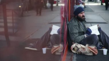Sad,tired homeless begs alms in the street,profile