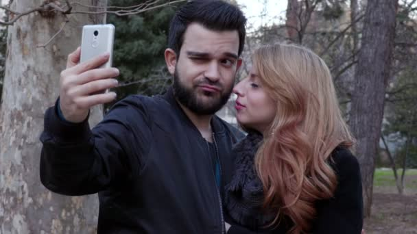 happy beautiful couple taking funny selfie at the park,winter time