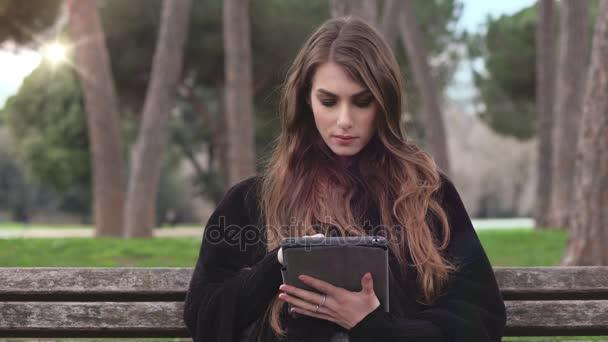 beautifu junge Frau sitzt Bank mit Tablet, im Freien