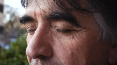 Thoughtful mature man opens his eyes,slow motion