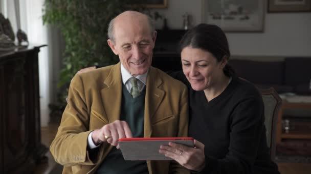 Vater und Tochter schauen sich Fotos auf dem Tablet an und lächeln