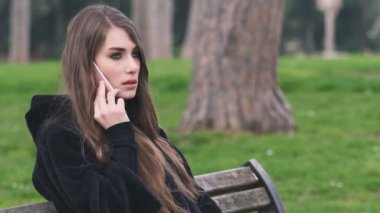 Young beautiful woman on bench talking by phone